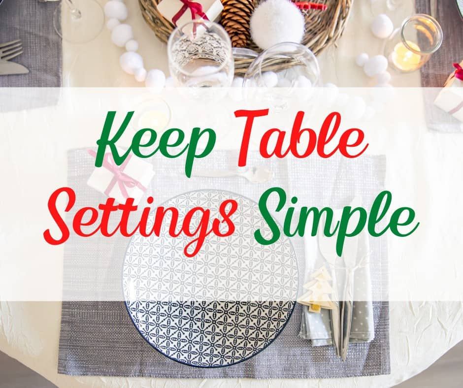 simple Christmas table setting with plate, flatware, cups, gifts, and candles